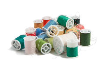 many spools of thread colors isolated on white background