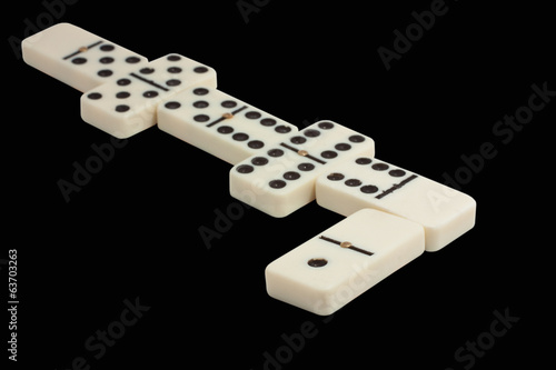 white line of dominoes isolated on a black background