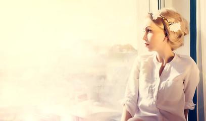 beautiful woman looking trough window