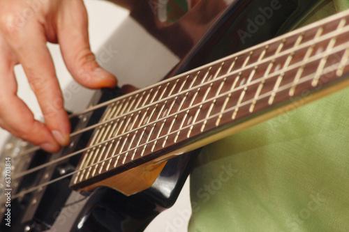 Guitarist playing the electric bass guitar closeup