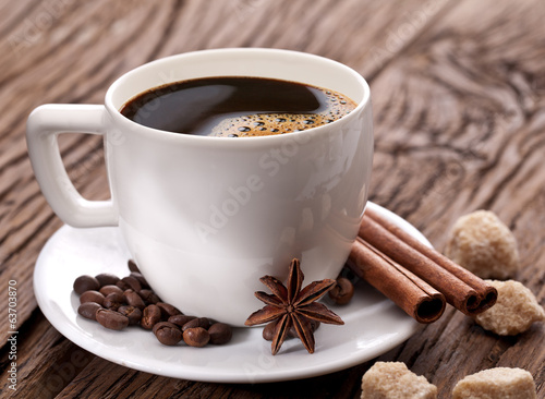 Cup of coffee with coffee beans and spices near it.