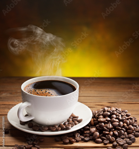 Cup of coffee with coffee beans near it.