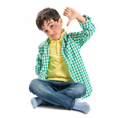 Kid making bad sign over white background