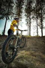 young man and mountain bike on jungle track use for sport activi