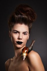 Portrait of a woman with snail with black eyes and lips. Fashion