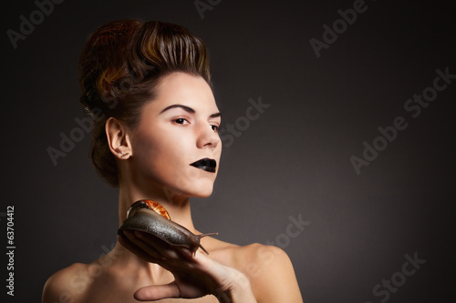 Brunette woman with snail with black eyes and lips. Fashion. Got