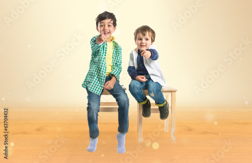 Boys pointing to the front over ocher background