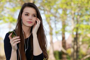 Jeune femme brune écoutant de la musique assise dans un pré