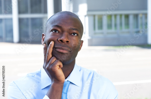 Thinking african businessman in front of his office