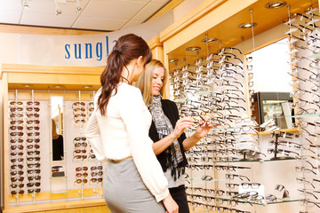 Optician and customer checking out glasses
