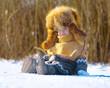 Ребенок в шапке-ушанке сидит