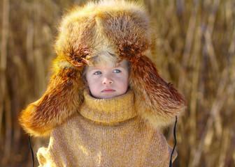 Серьезный ребенок в шапке-ушанке