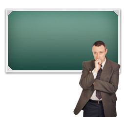Teacher standing near clean chalkboard