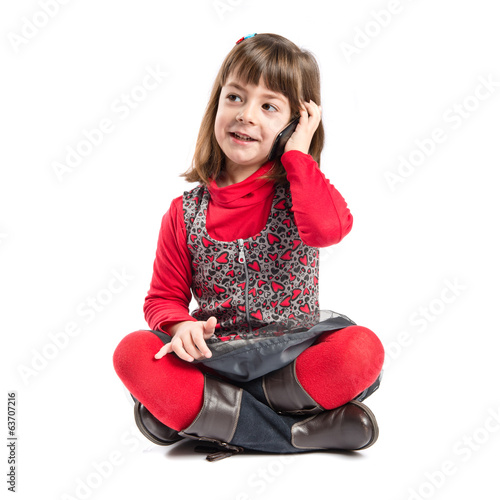 Child talking to mobile over isolated background.