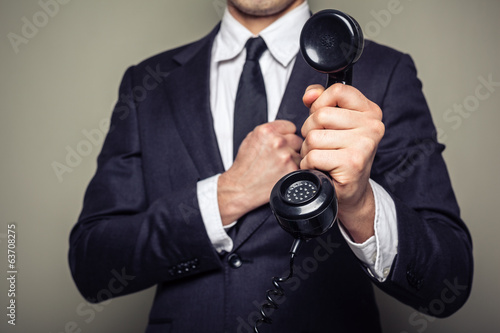 Businessman handing over a telephone