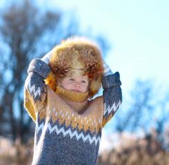 Ребенок в меховой  шапке держится за голову