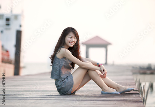 beautiful asian woman sitting on wood pier with relaxing emotion