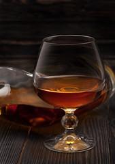 Glass of Cognac brandy on a dark wooden background