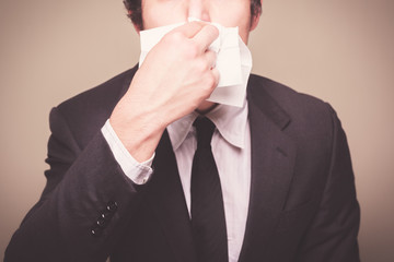 Businessman blowing his nose