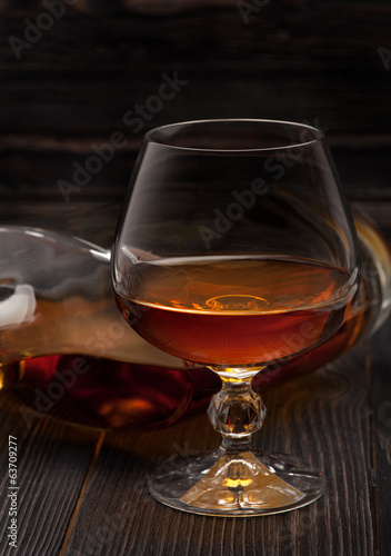 Glass of Cognac  brandy on a dark wooden background