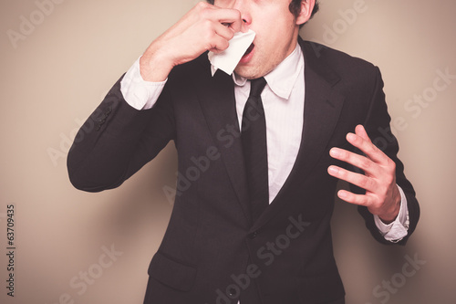 Businessman sneezing