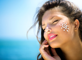 Beauty Girl Applying Sun Tan Cream on her Face. Sun Tanning