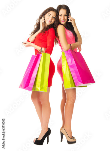 Two young girls with mobile phones and bags