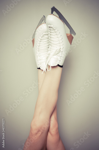 Woman wearing ice skates against a wall