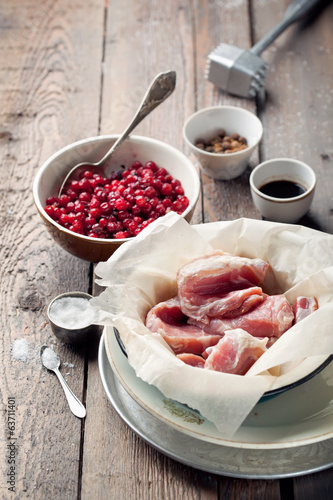 Raw pork in a basin, cowberries, seasonings and meat hammer on w