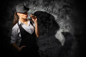 Woman with cigar on grey wall