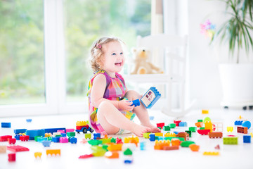 Adorable laughing toddler girl playing with colorful blocks sitt