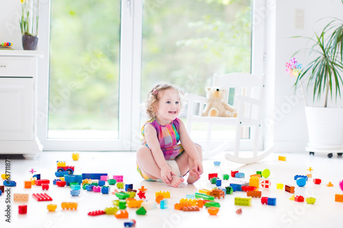 Adorable curly toddler girl playing in messing nursery