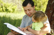 young father with his little daughter reads the Bible