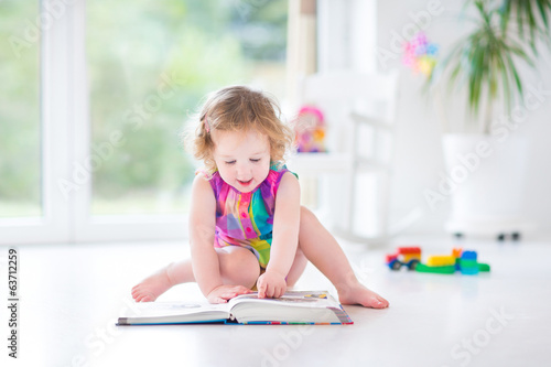 Funny toddler girl reading book sitting on a fllor in nursery