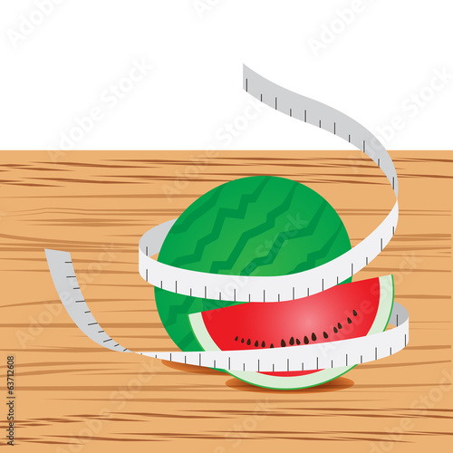 Watermelon with measure tape and table wood
