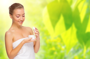 Healthy woman with bady cream on spring background