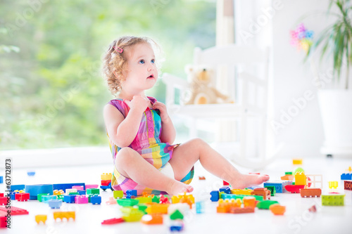 Beautiful toddler girl with curly hair sitting on a floor