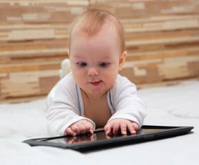 Полугодовалый ребенок изучает современный планшет