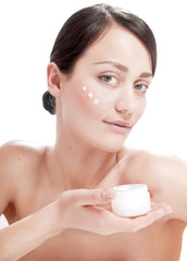 Beautiful woman applying cosmetic cream treatment on her face.