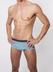 Oberkörper eines nackten Mannes in Badehose