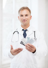 young male doctor with packs of pills