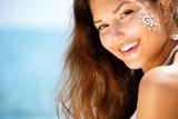 Beauty Girl Applying Sun Tan Cream on her Face. Sun Tanning