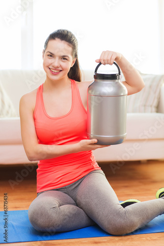 smiling teenage girl with jar of protein at home