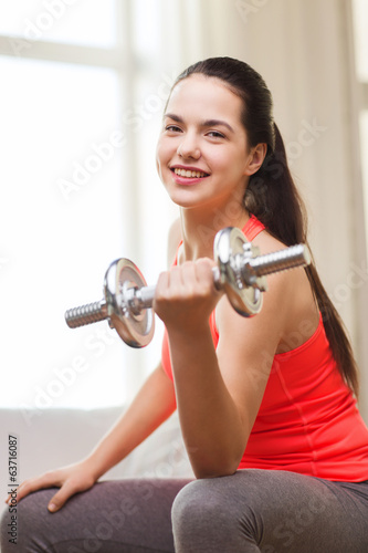 smiling girl exercising with dumbbells