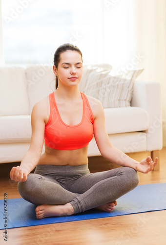 smiling teenager meditating at home