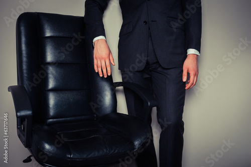 Businessman standing by office chair