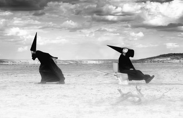 Two strange persons in black cloaks traveling in the desert