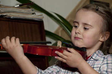 cute 3 year old  girl learning violin playing at music school
