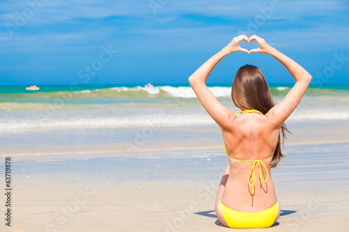 Back view young long haired woman in yellow bikini in hair