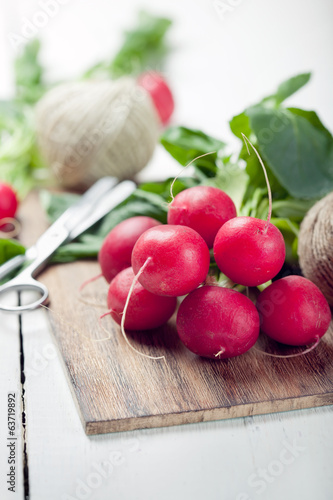 Bunch of fresh organic radish on wooden chopping board